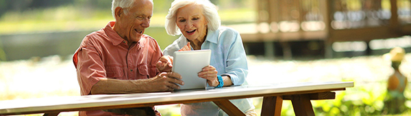Elder couple sitting outside and looking at their tablet