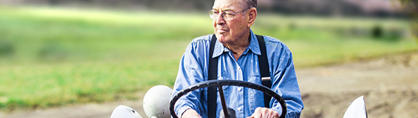Older man driving outdoor equipment
