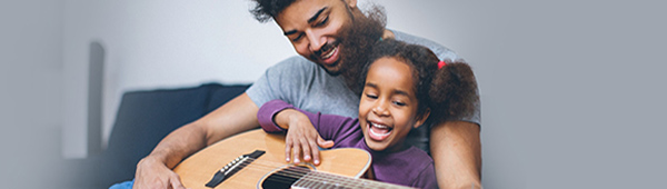 Dad showing young daughter how to play guitar