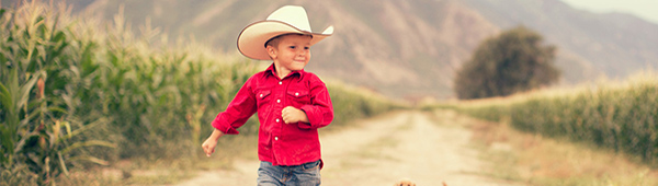 Young boy with cowboy hat on farm